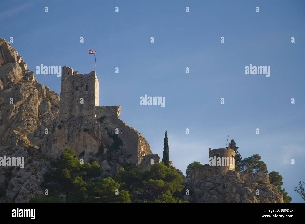 Defensive fortress with croatian flag on mountains in summer sunshine Omis Dalmatian Coast Croatia Dalmatia - Stock Image