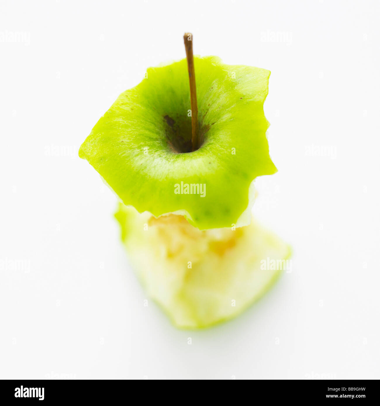 An apple core isolated on a white background, shot with shallow focus to emphasise the strong graphic shape. - Stock Image