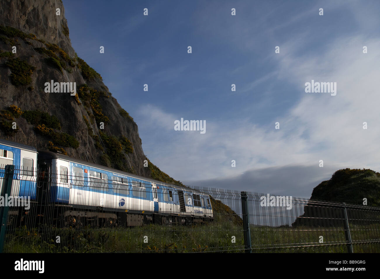 northern ireland railways train travelling past white head rocks in whitehead on the belfast to larne train route - Stock Image