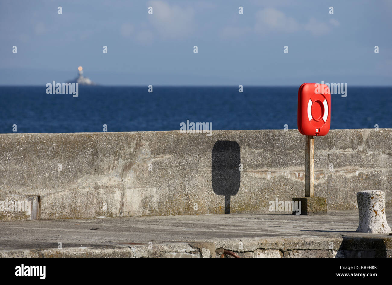 lifebelt on the quay wall at portmuck harbour with the maidens lighthouse in the distance islandmagee county antrim - Stock Image