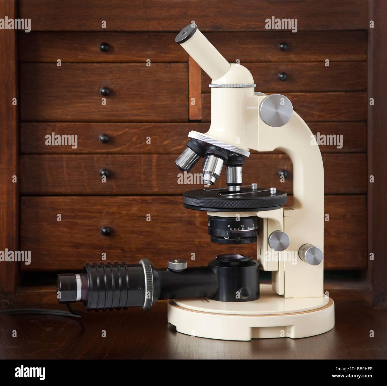 Wild Heerbrugg M11 compound microscope (1954), wooden drawers background, kohler lighting unit - Stock Image
