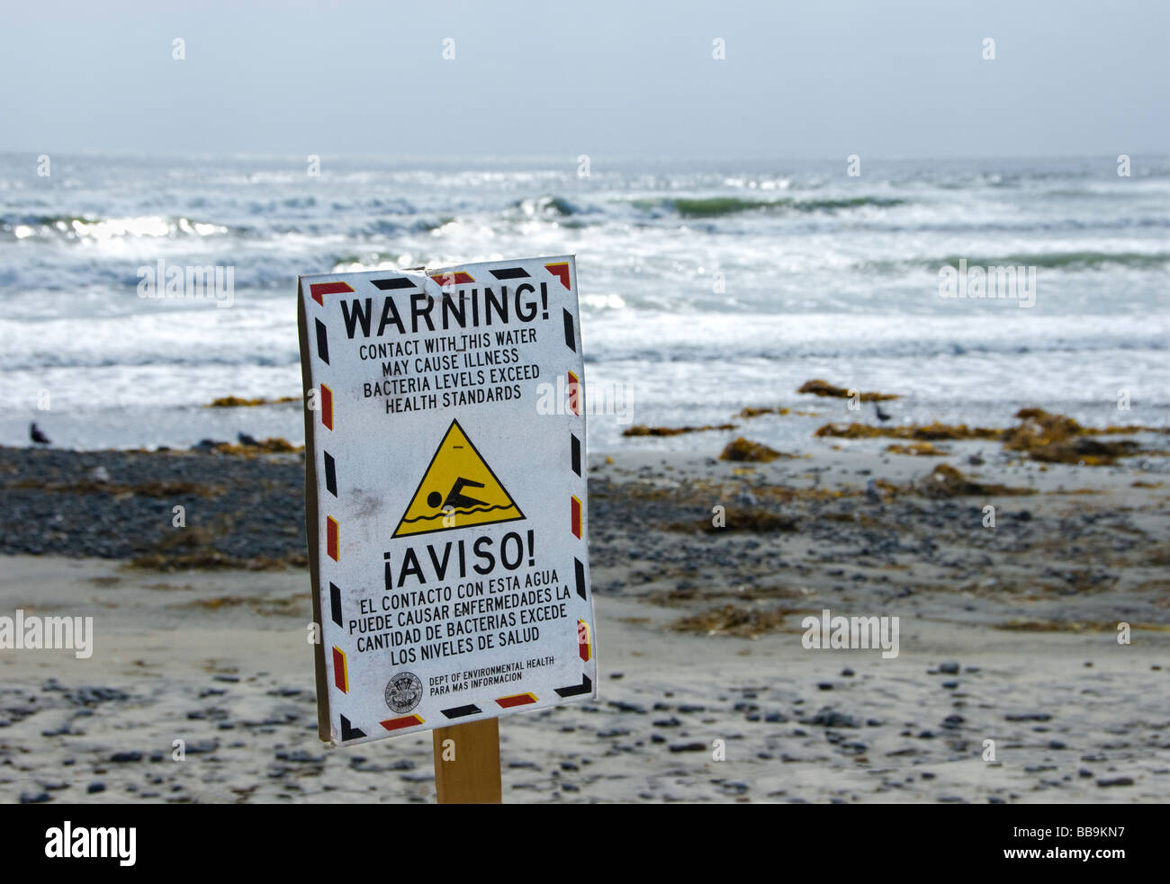 Sign on beach warning people of possible contaminated ocean water.  Sign is written in both english and spanish. - Stock Image