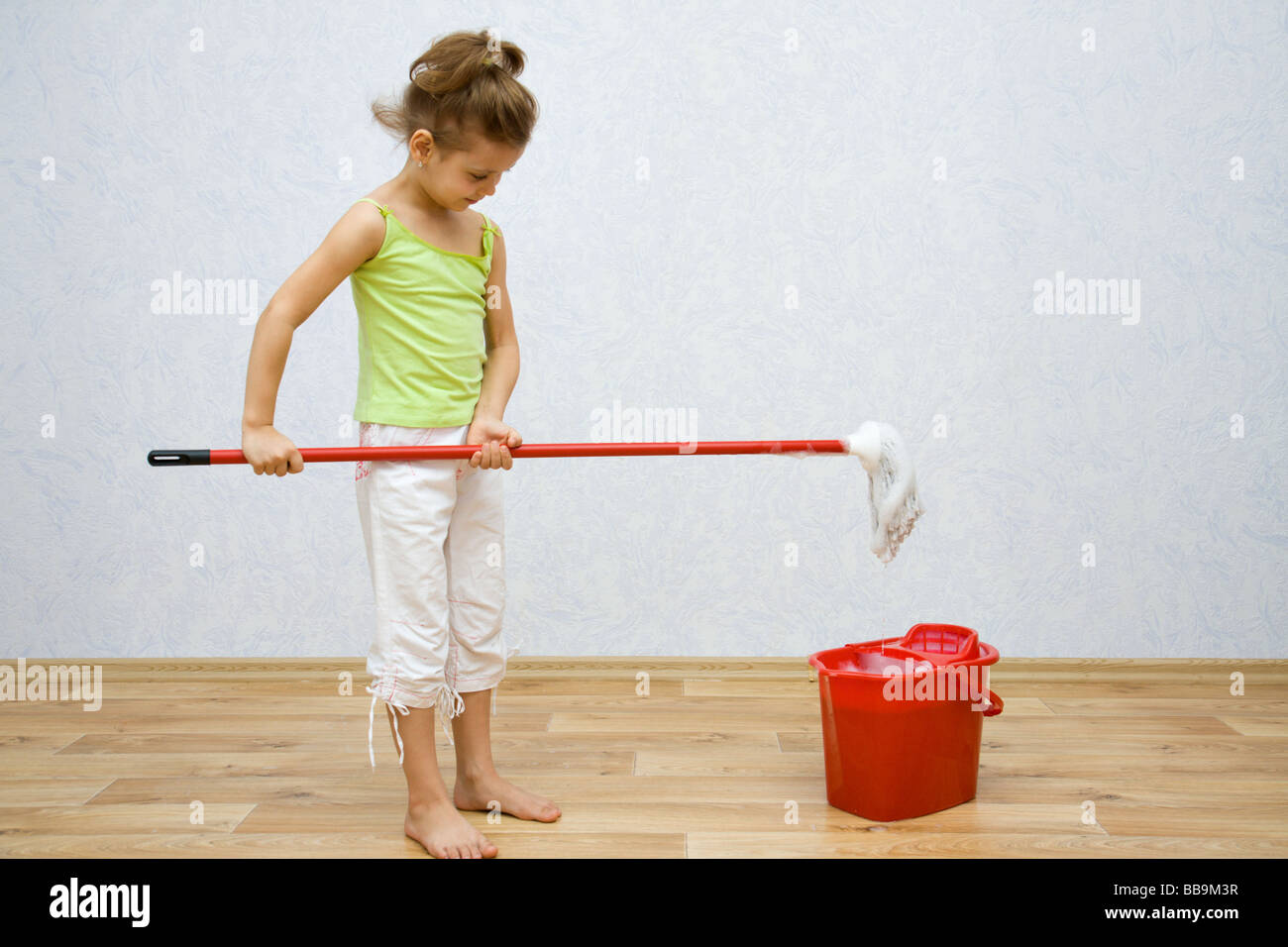 Little girl cleaning the floor in the room - Stock Image