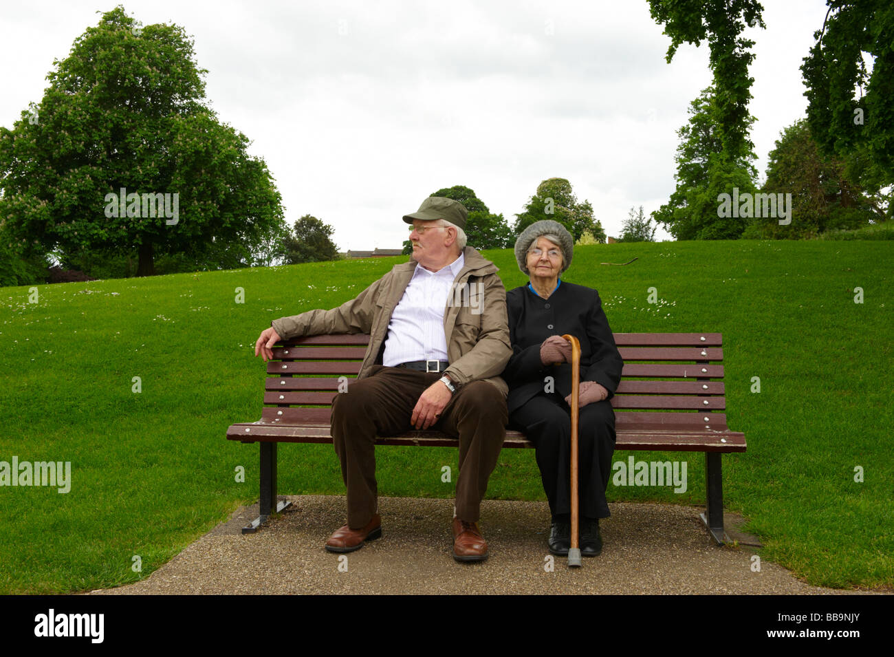 Elderly married couple sitting on park bench - Stock Image