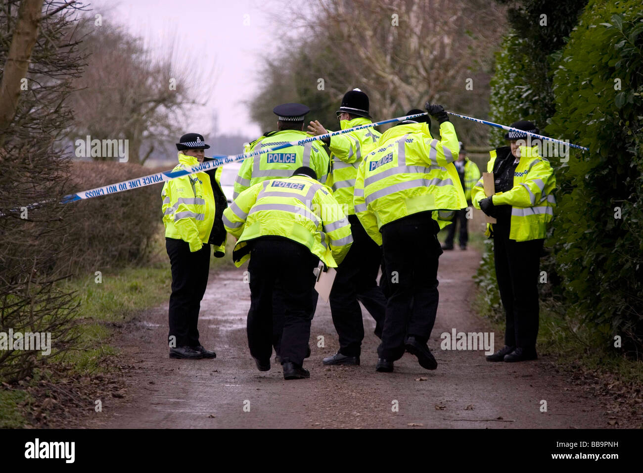 Police in yellow flourescent jackets cross a police tape line on the way to search for clues after the discovery - Stock Image