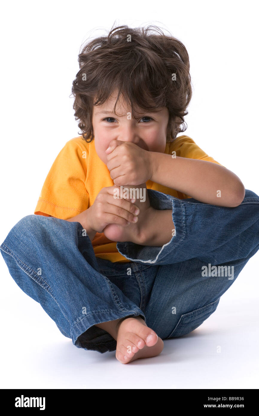 Little boy eating his large toe as a joke - Stock Image