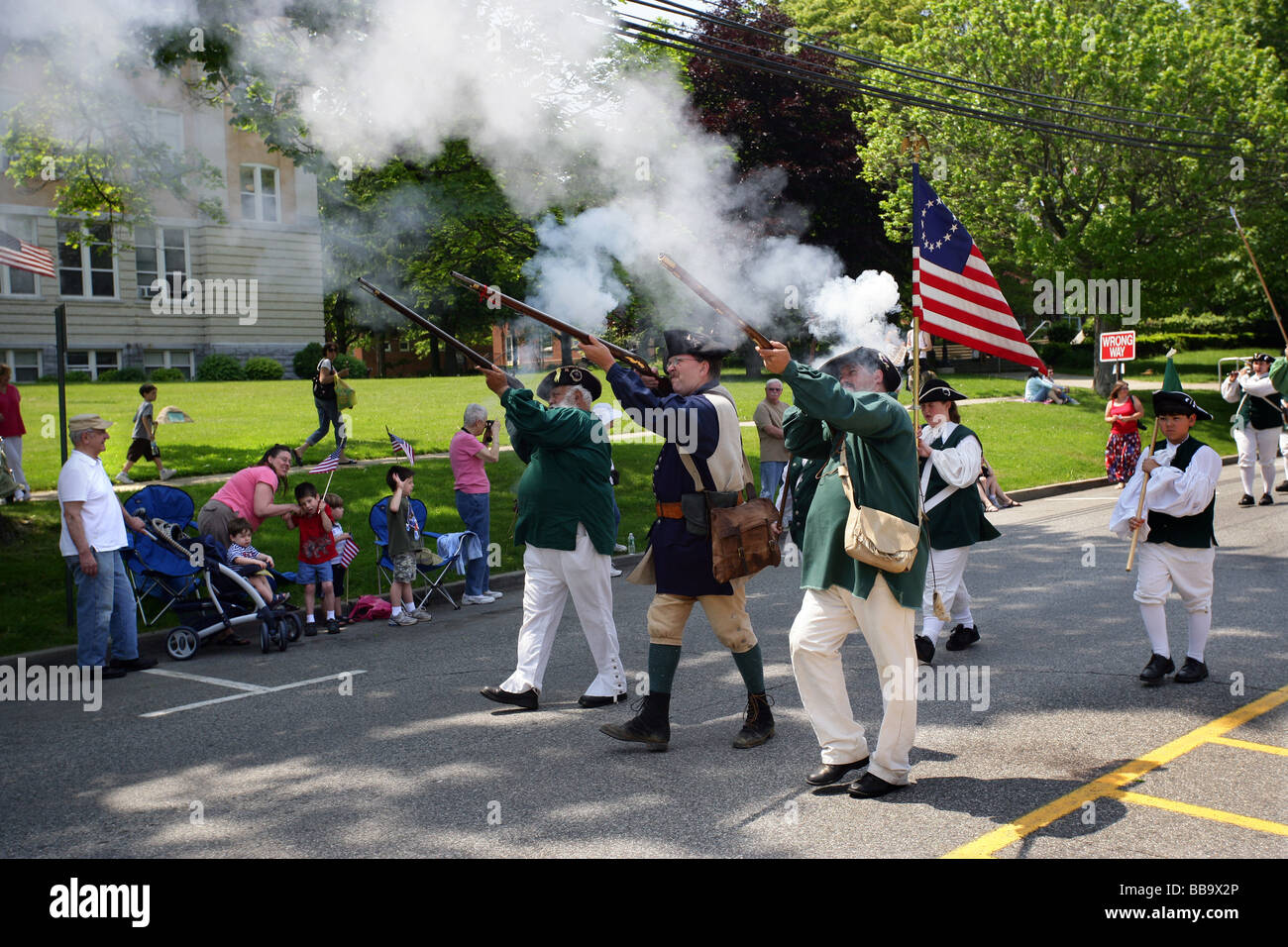 Colonial Minutemen shoot their muskets as they march in a Memorial day parade in Milford CT USA - Stock Image