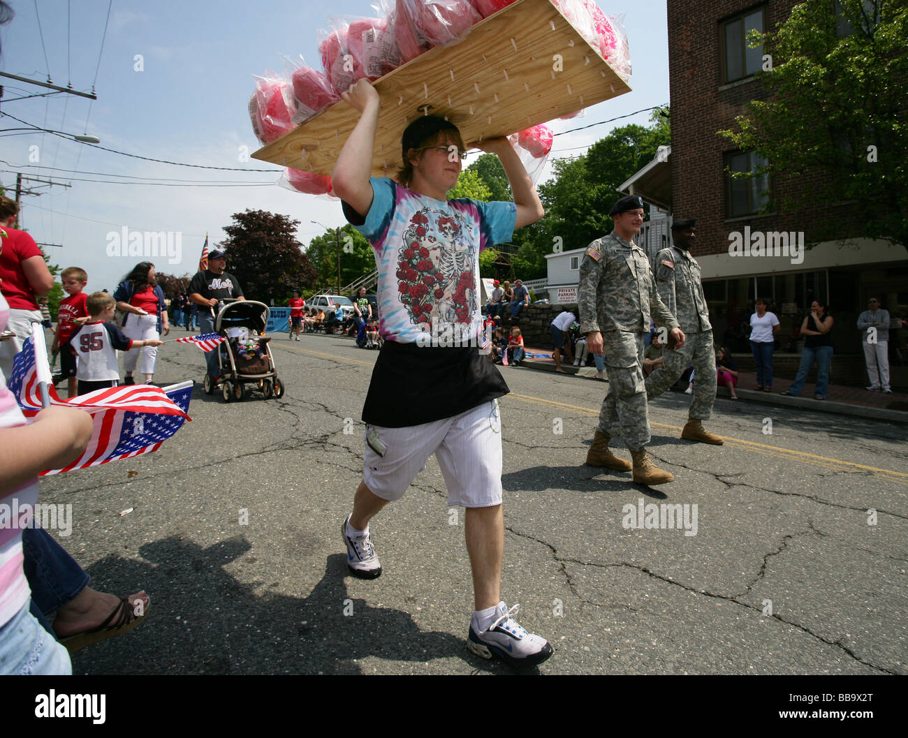 A Cotton Candy seller walks along during a Memorial Day Parade in Seymour CT USA. Typical American summer parade - Stock Image