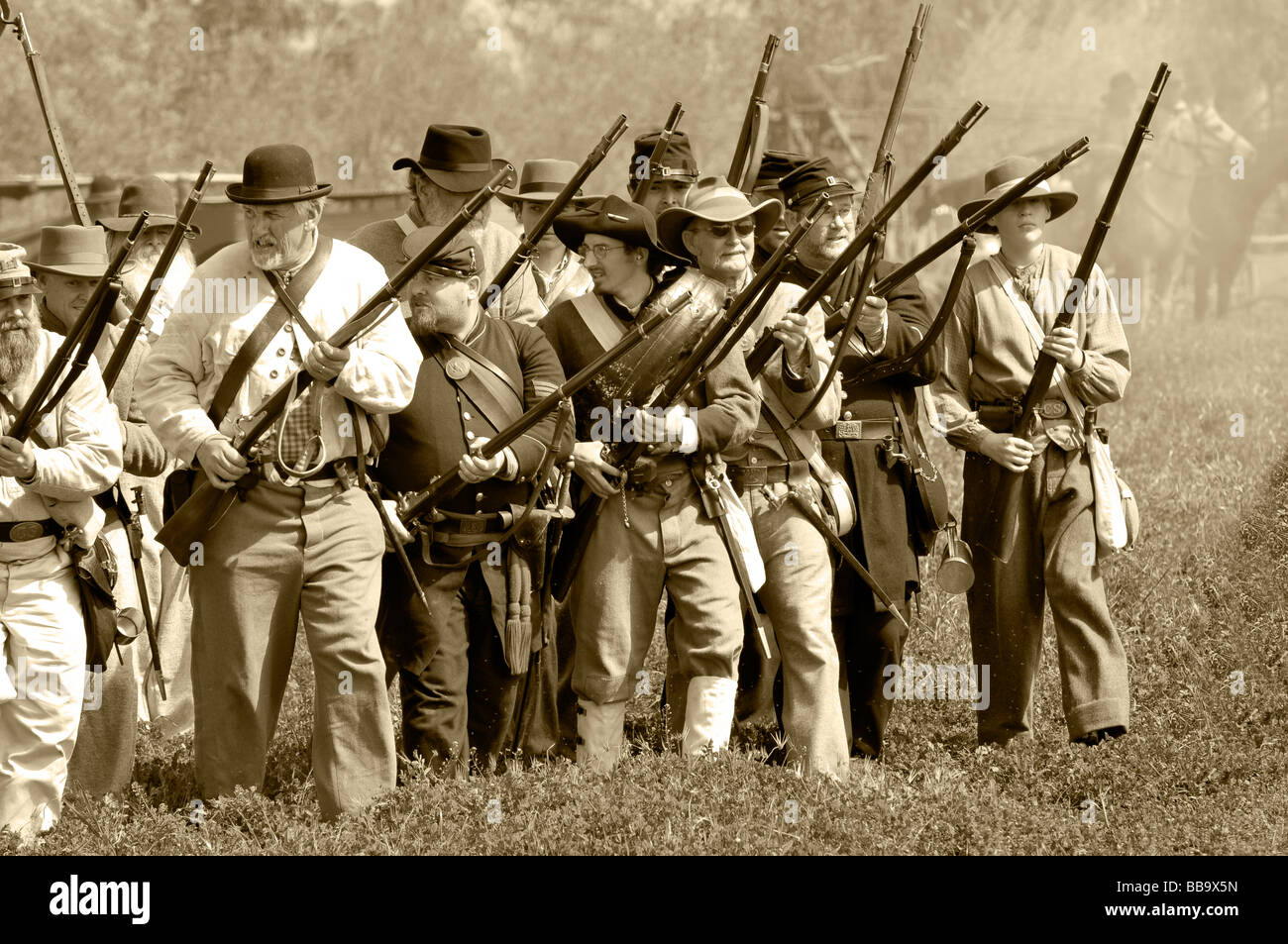 Confederate soldiers on the battlefield with muskets in sepia tones during a civil war re-enactment. - Stock Image
