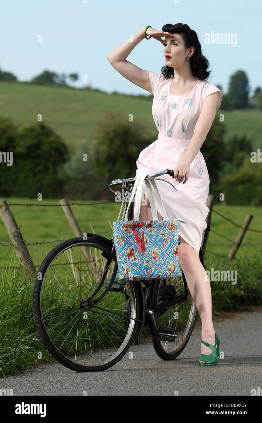 Woman wearing vintage clothing on an old bicycle - Stock Image