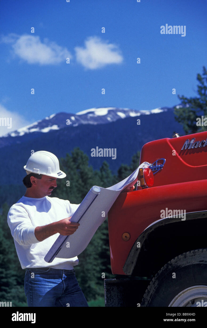 Contractor checking blueprints at construction site, Whistler, BC, Canada. - Stock Image