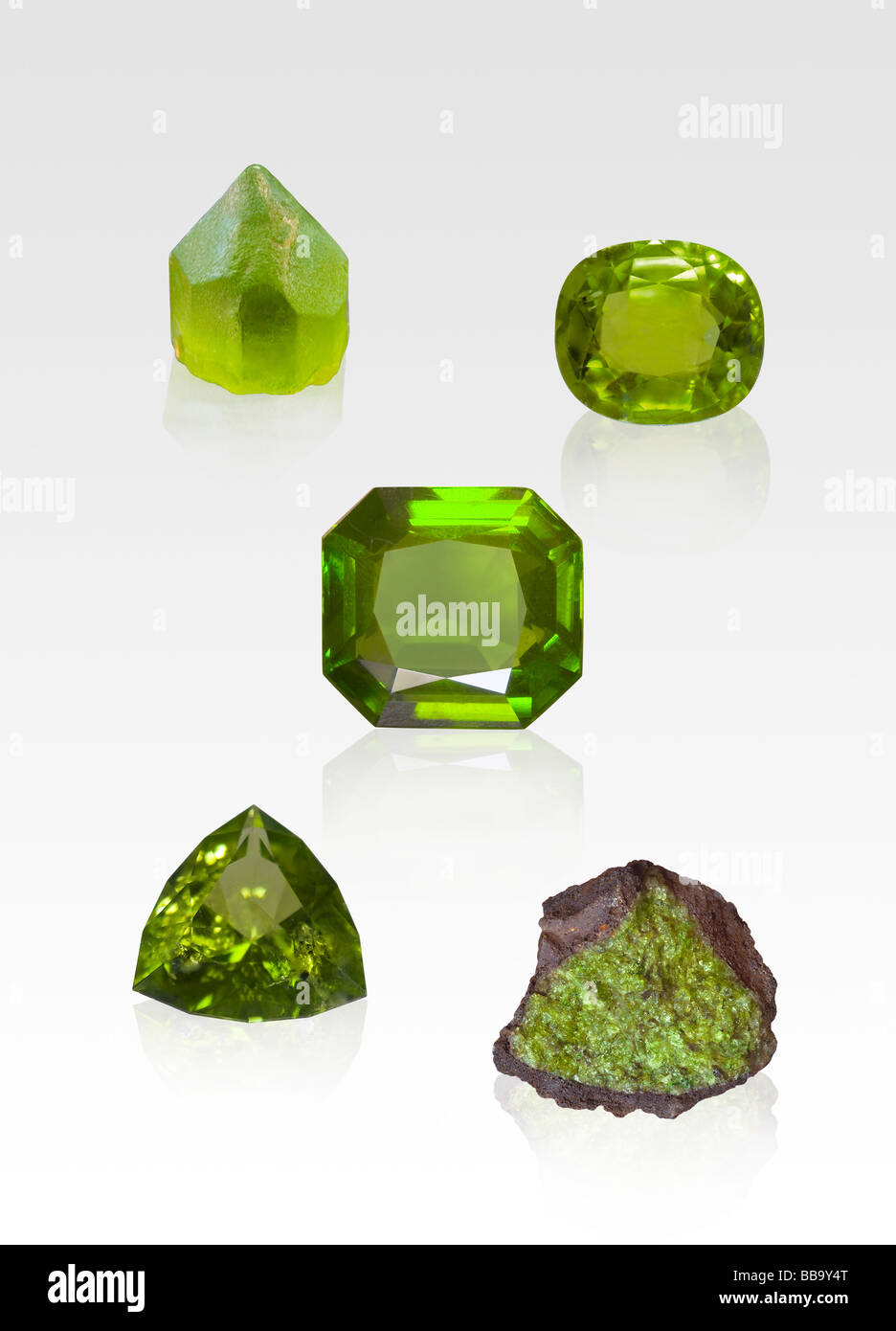 Peridot gem and crystal specimens on white background - Stock Image
