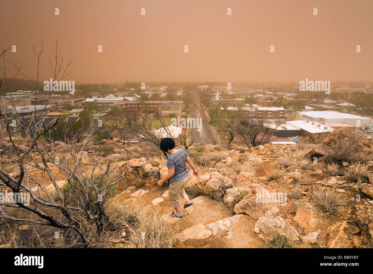 A woman descends from Anzac Hill as a dust storm hits the outback town of Alice Springs.  Alice Springs, Northern - Stock Image
