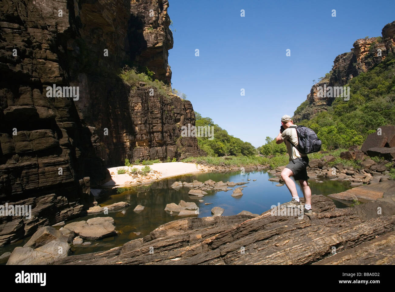 A tourist photographs Jim Jim Gorge.  Kakadu National Park, Northern Territory, AUSTRALIA - Stock Image