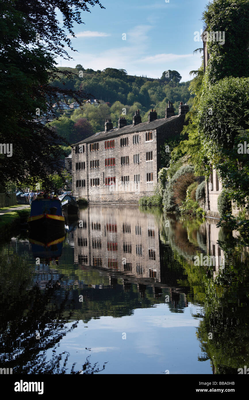 Old cotton mills reflected in the Rochdale Canal at Hebden Bridge in West Yorkshire - Stock Image