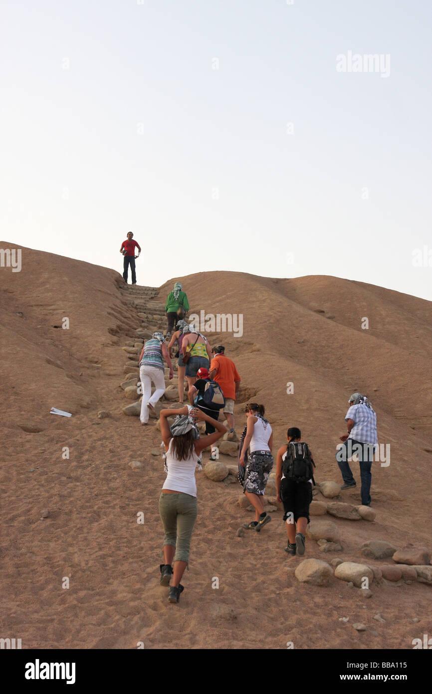 group of tourists climbing sand dune in sinai desert - Stock Image