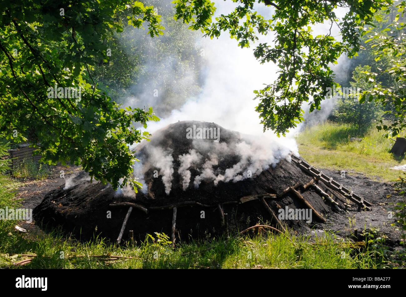 Glimmering charcole pile in Siegerland near Netphen, North Rhine-Westphalia, Germany - Stock Image