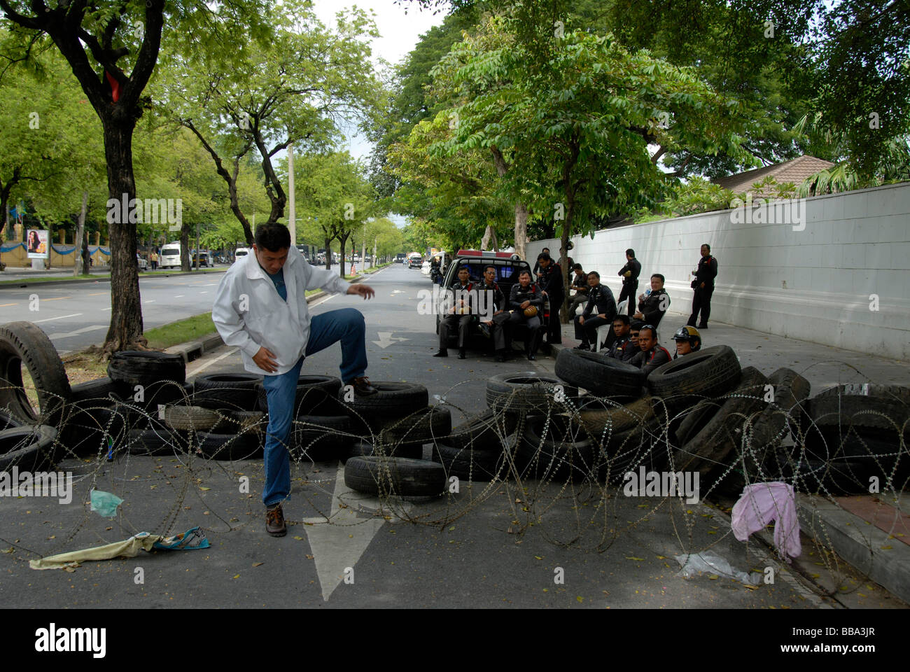 Demonstration, man overcoming barbed wire and car tires roadblock, police watching interestedly, Bangkok, Thailand, - Stock Image