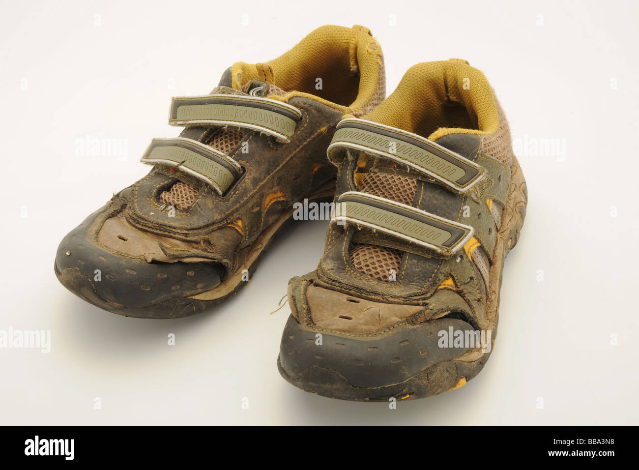 A pair children's worn out trainers - Stock Image
