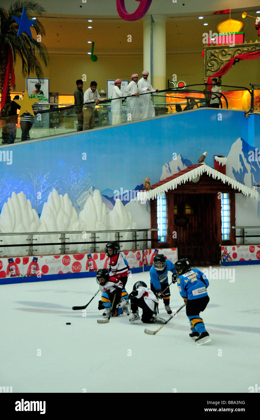 Arabs in Dishdashas, the typical white garments, watching kids playing ice hockey on the ice rink of the Al Ain - Stock Image