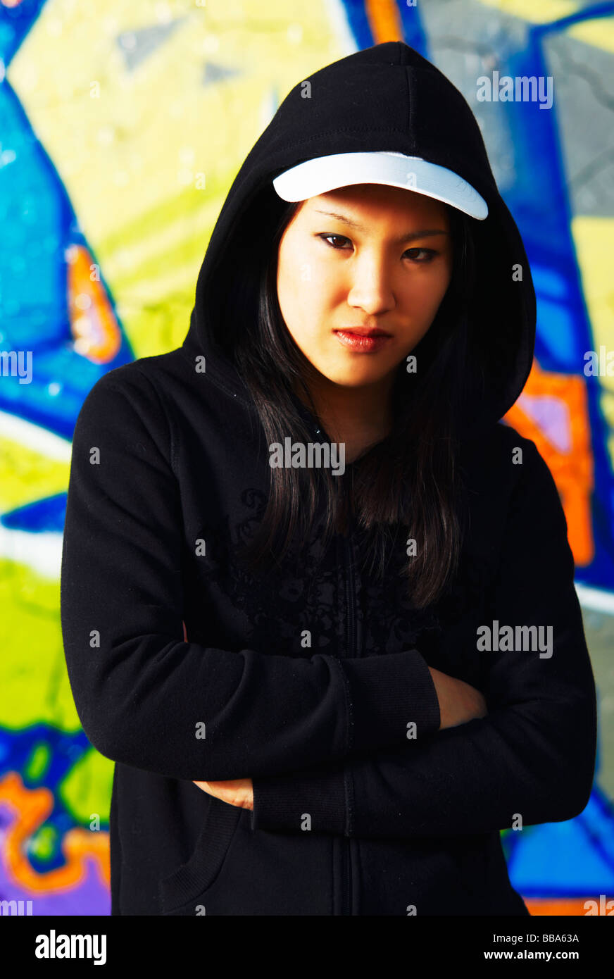 Young Asian girl in rapper pose in front of a graffiti wall - Stock Image