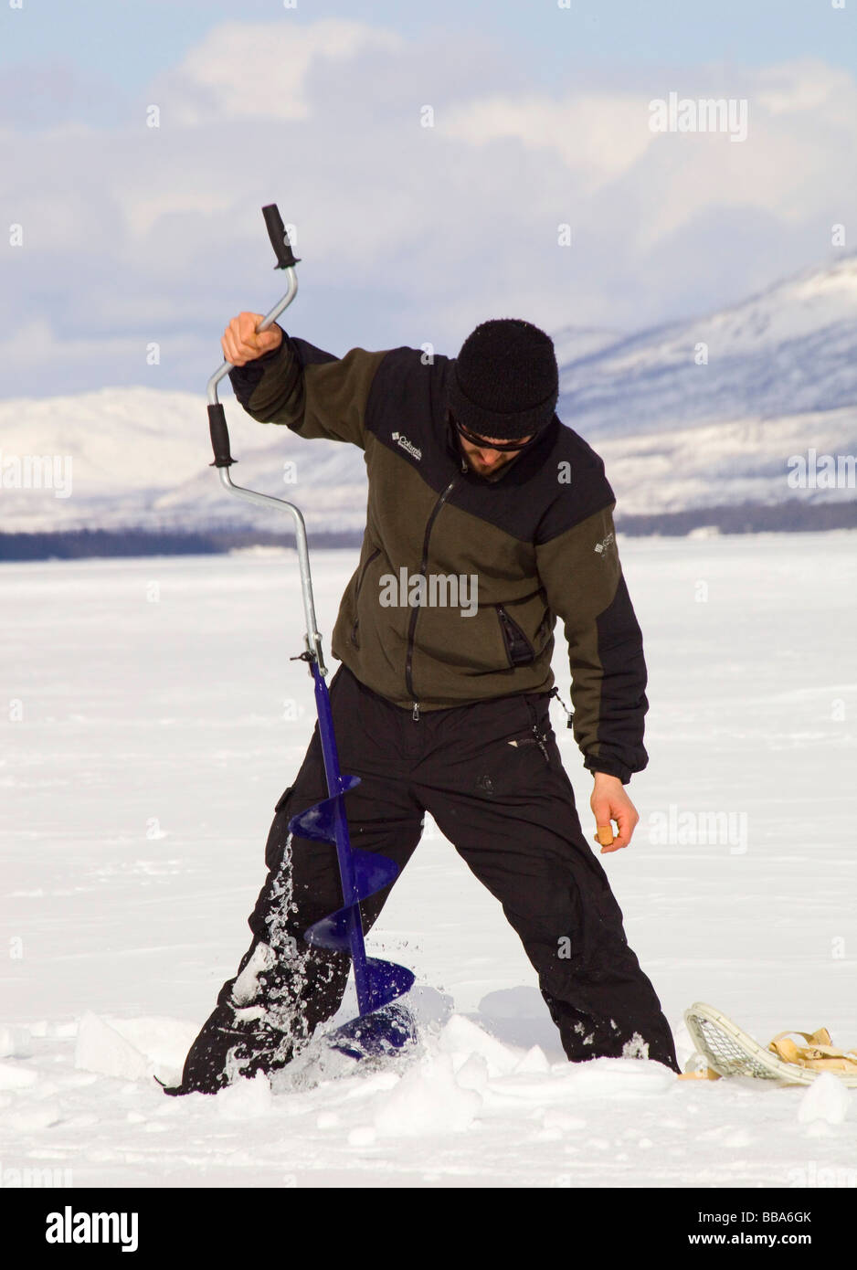 Man ice fishing, drilling a hole with an ice auger, Fox Lake, Yukon