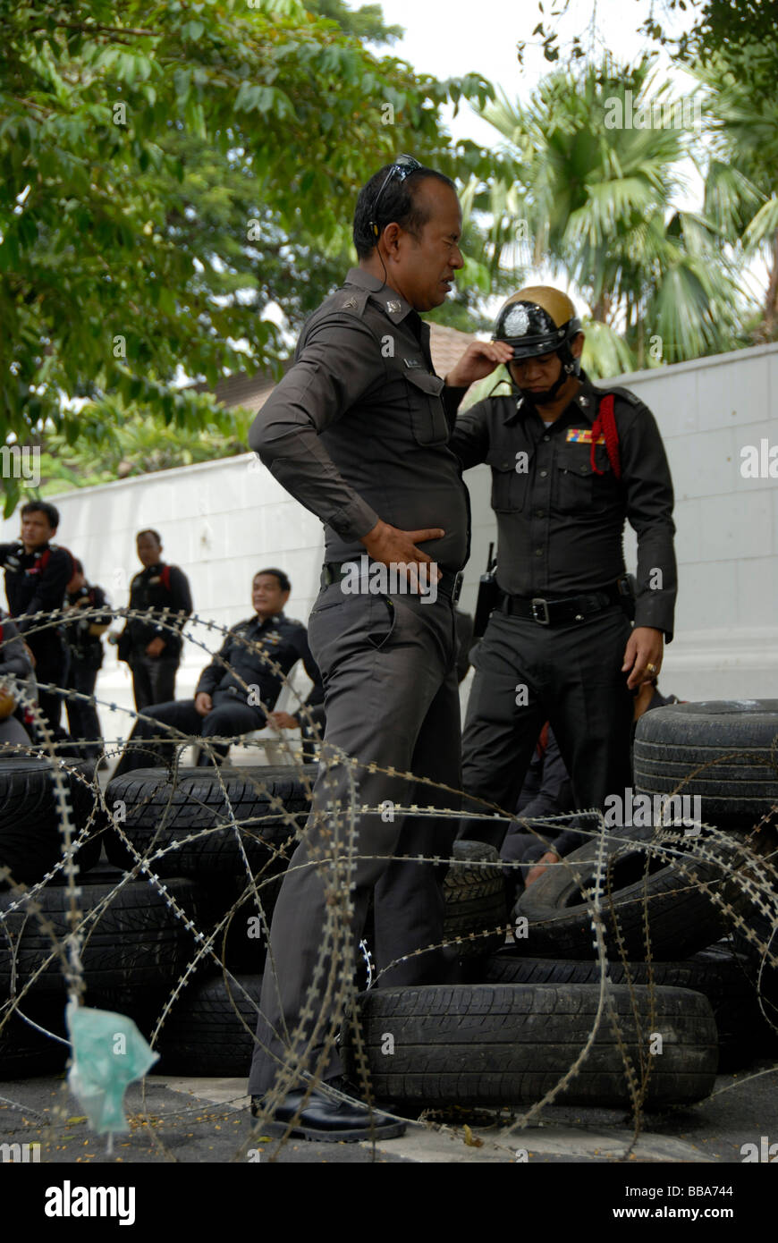 Demonstration, police standing at roadblock of barbed wire and car tires, Bangkok, Thailand, Southeast Asia - Stock Image