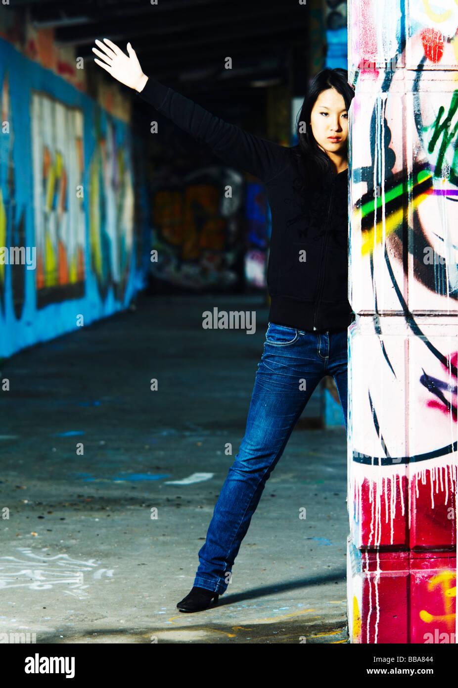 Young Asian girl in rapper pose between walls with graffiti - Stock Image