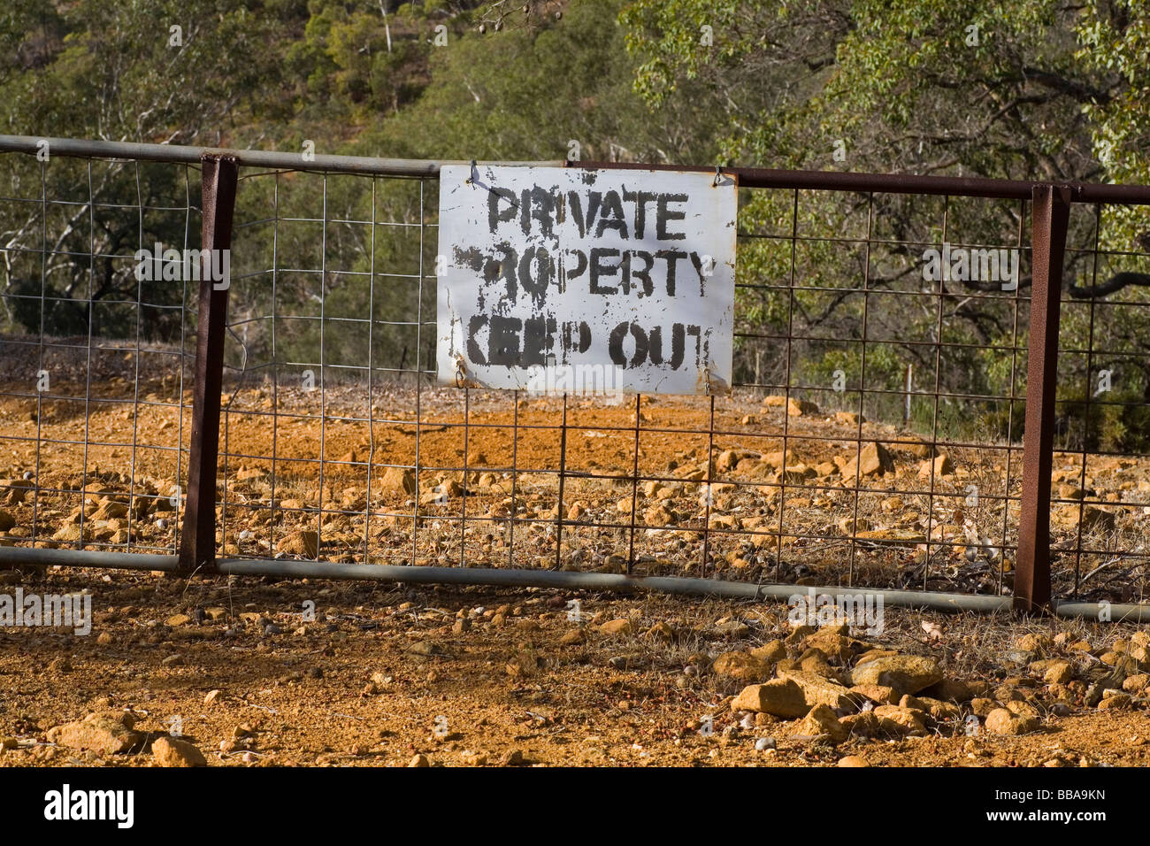 Worn old Keep Out Private Property sign in the Australian countryside - Stock Image