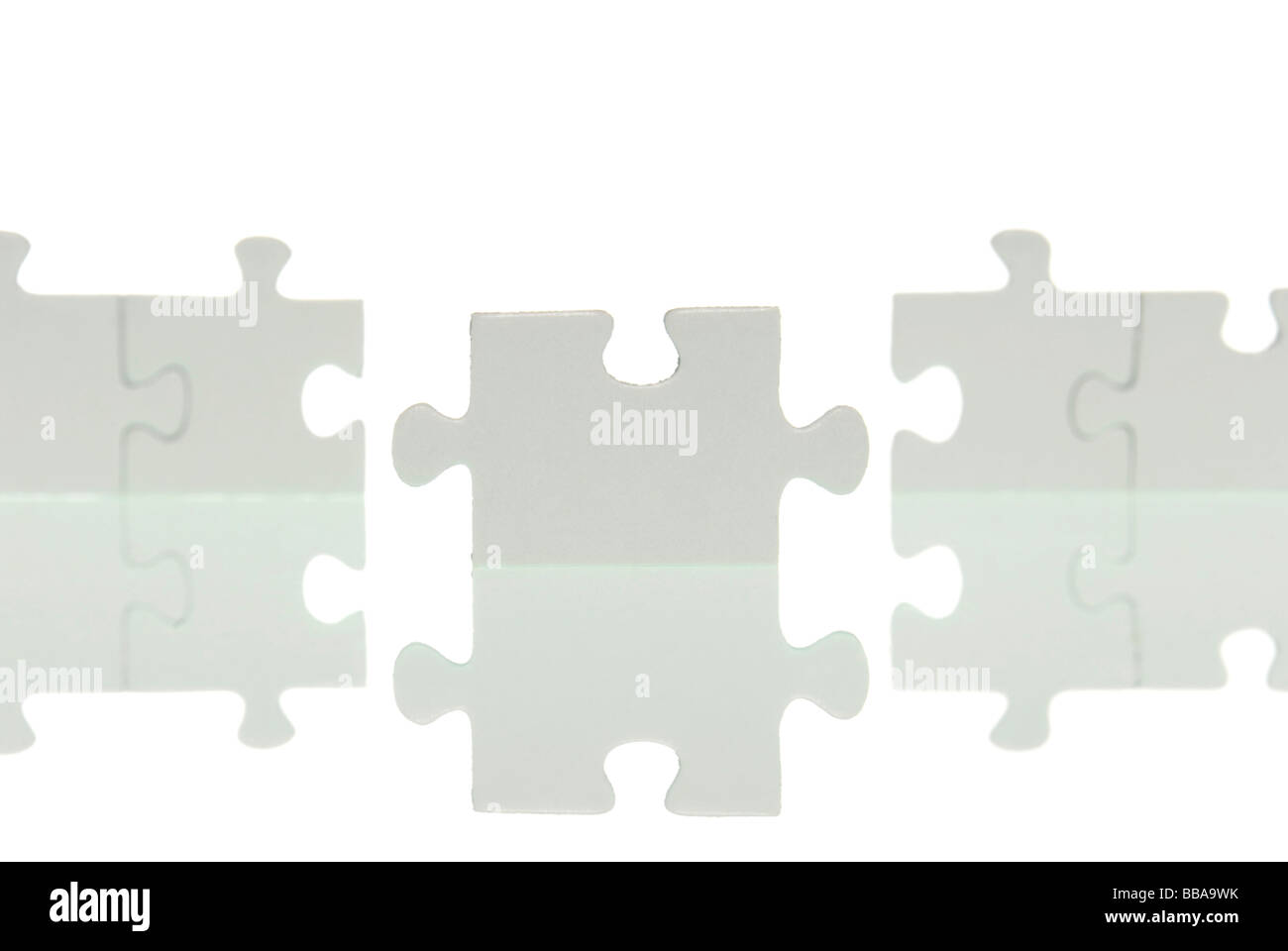 A row of puzzle pieces with a joining piece - Stock Image