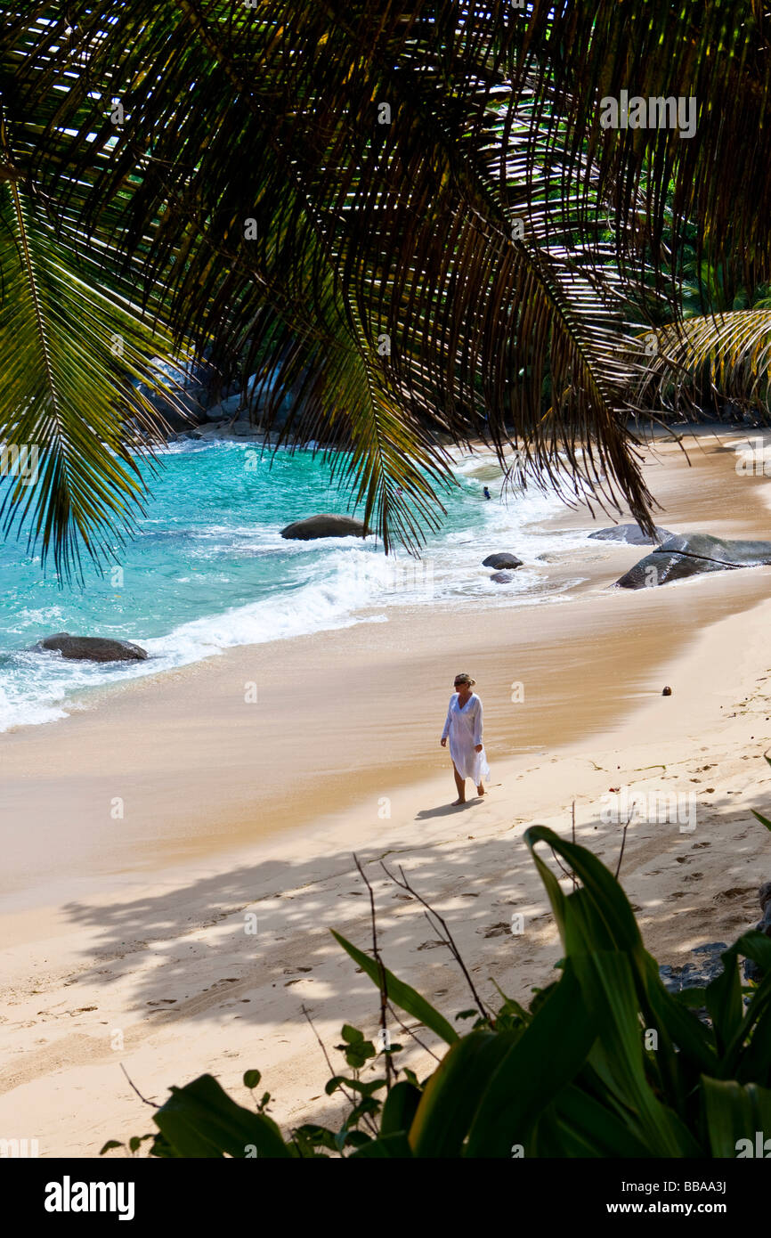 Woman walking along the beach wearing a tunic, Mahé Island, Seychelles, Indian Ocean, Africa - Stock Image