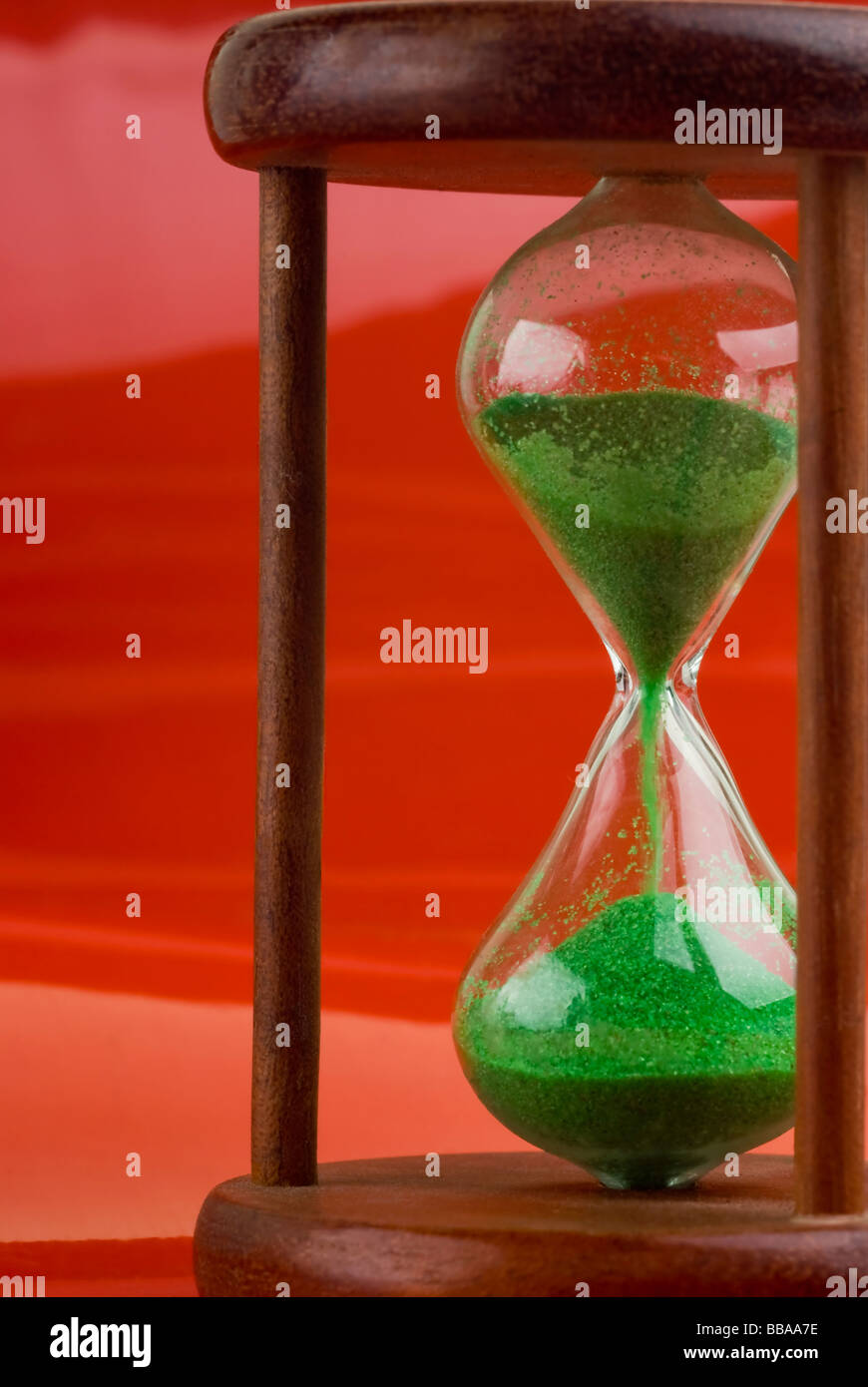 Close-up of an hourglass over a red background. - Stock Image