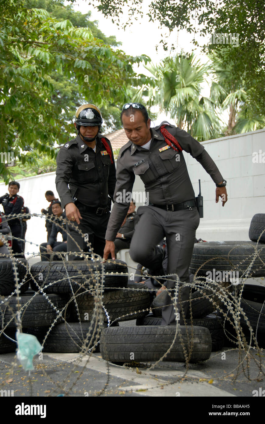 Demonstration, policemen climbing over roadblock of barbed wire and car tires, Bangkok, Thailand, Southeast Asia - Stock Image