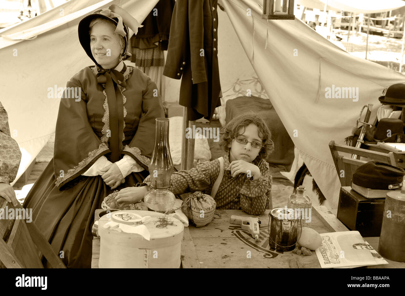 Civil War Family - encampment re-creation - a woman and child at the dinner table next to a tent. Sepia tones. Stock Photo