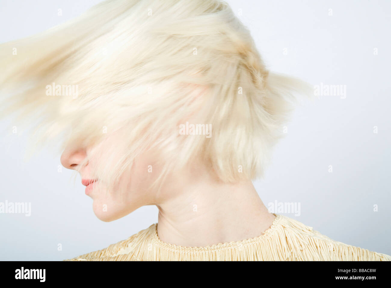 A young woman shaking her hair - Stock Image