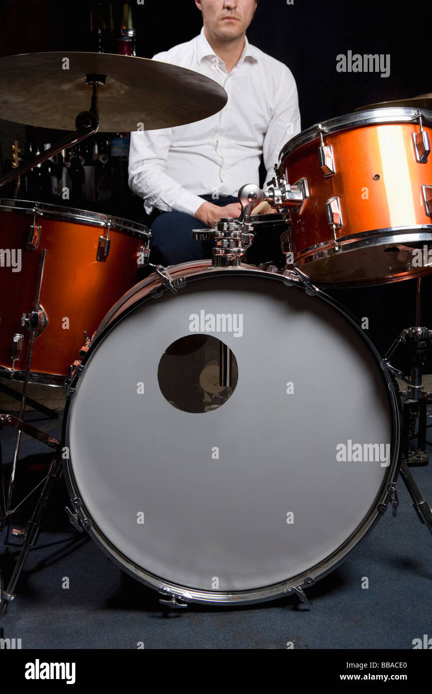 A man sitting at a drum kit - Stock Image