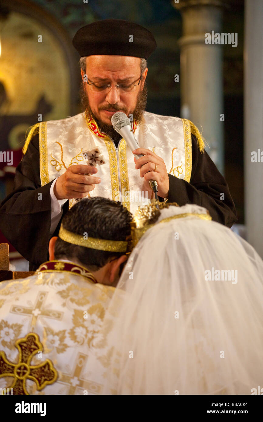 priest blessing bride and groom at Coptic wedding in Cairo, Egypt - Stock Image