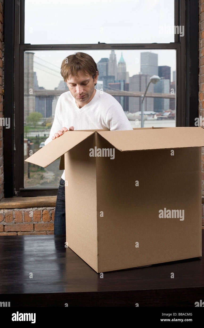 A man packing a cardboard box - Stock Image