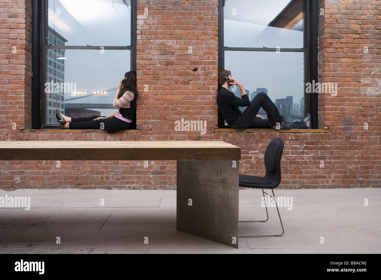 A man and woman sitting on window sills and talking on mobile phones - Stock Image