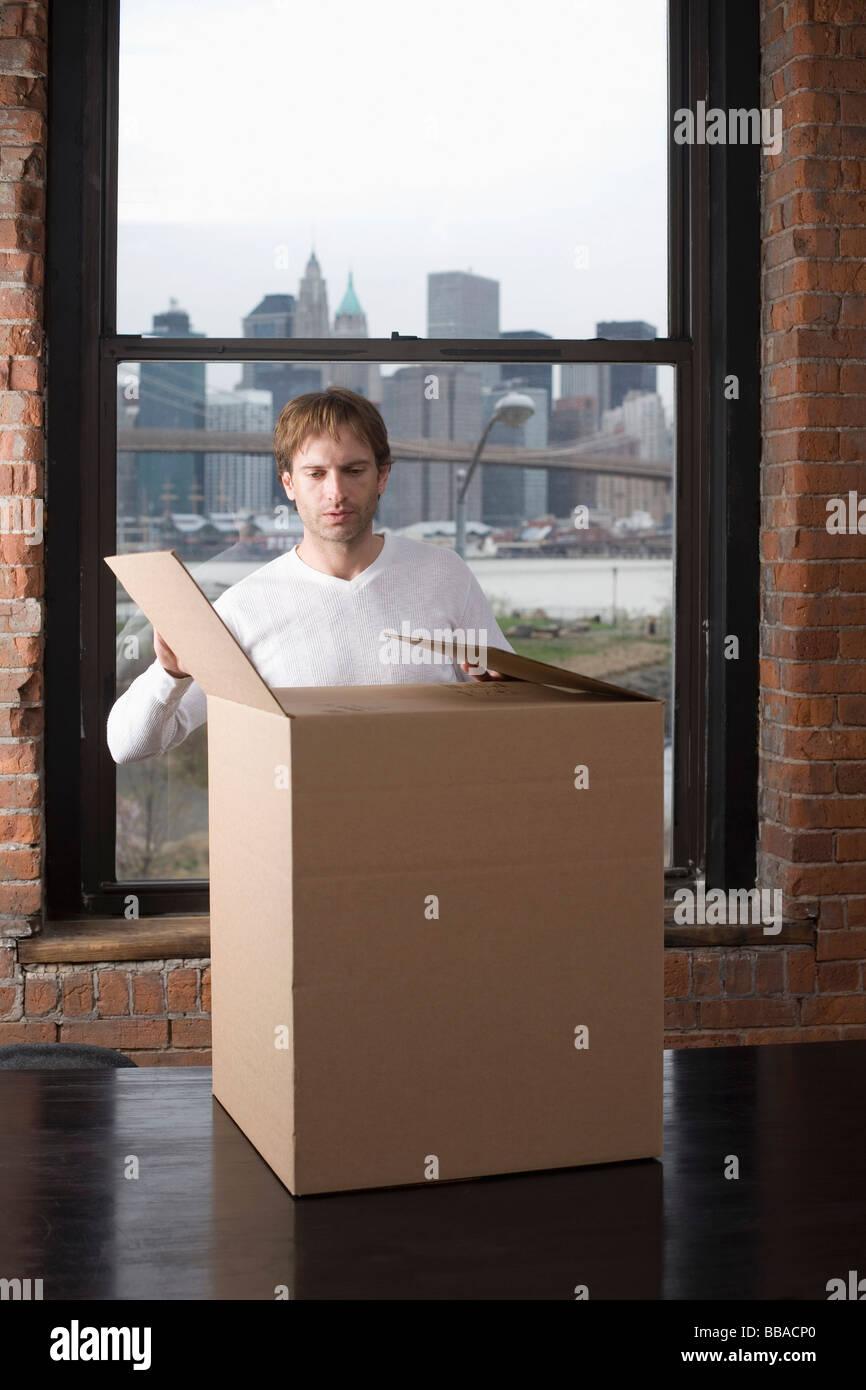 Man unpacking cardboard box in office - Stock Image
