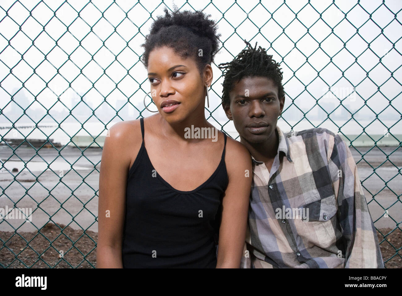 A young couple in front of a chainlink fence - Stock Image