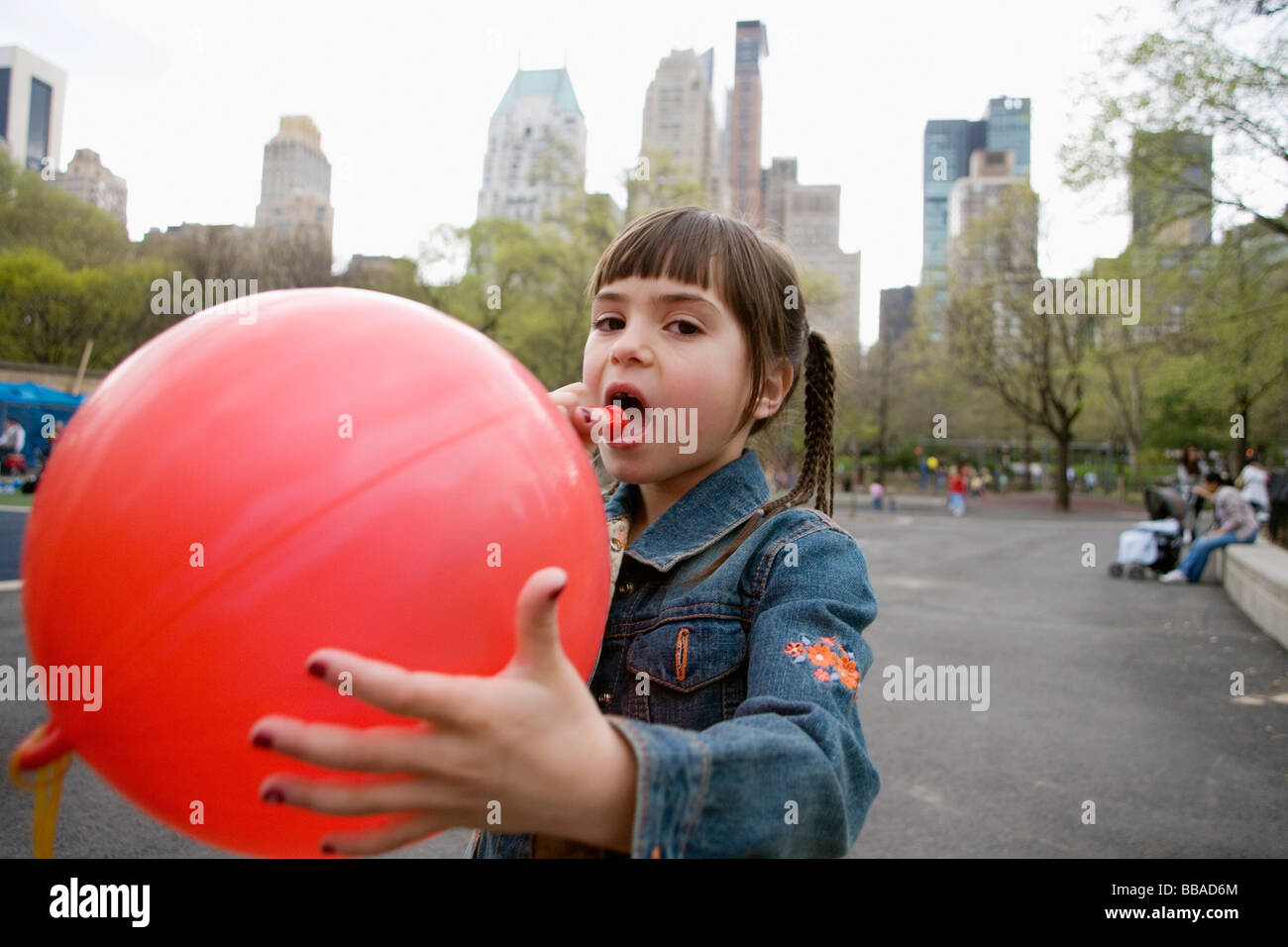 A young girl blowing up a balloon in Central Park, New York City - Stock Image