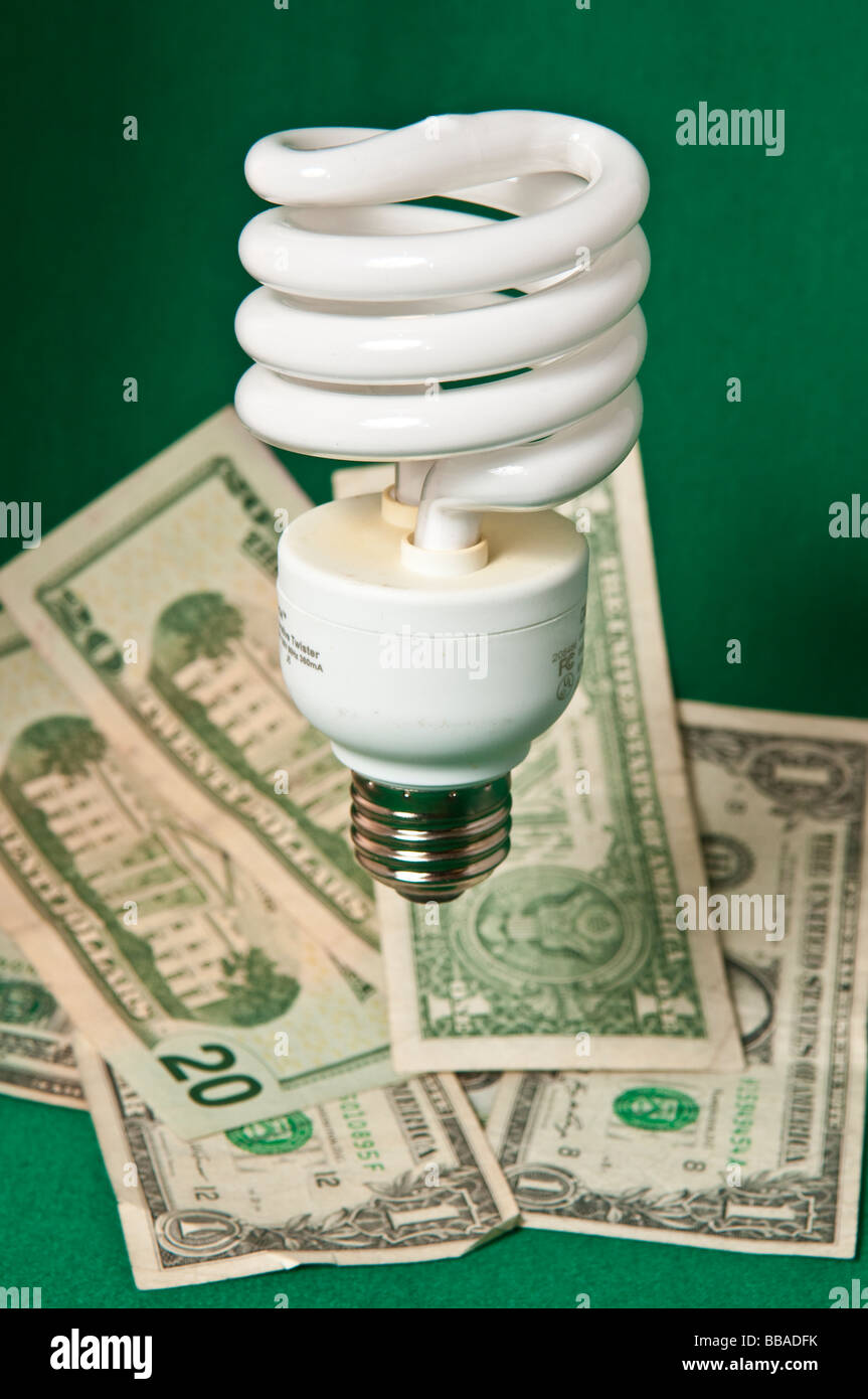 White Energy saving light bulb with paper money denoting savings - Stock Image