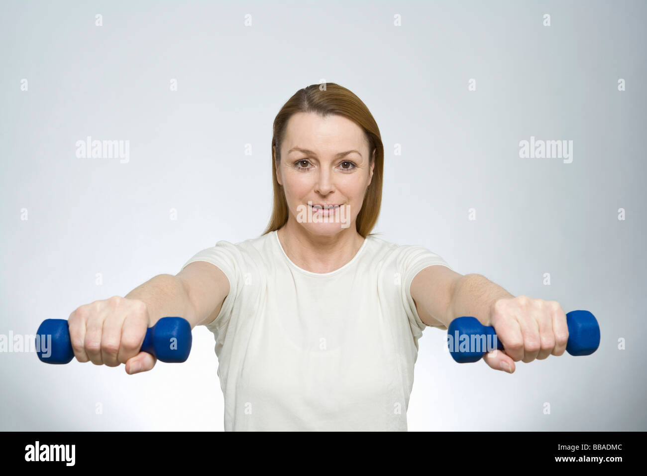 A woman lifting dumbbells - Stock Image