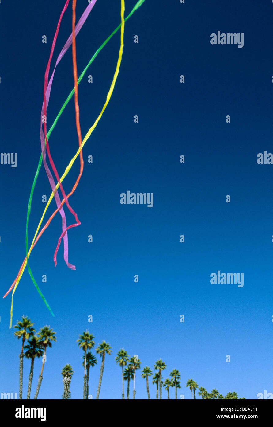 Colored streamers floating in the sky above palm trees - Stock Image