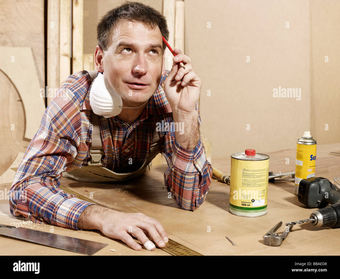A man leaning on a workbench and thinking - Stock Image