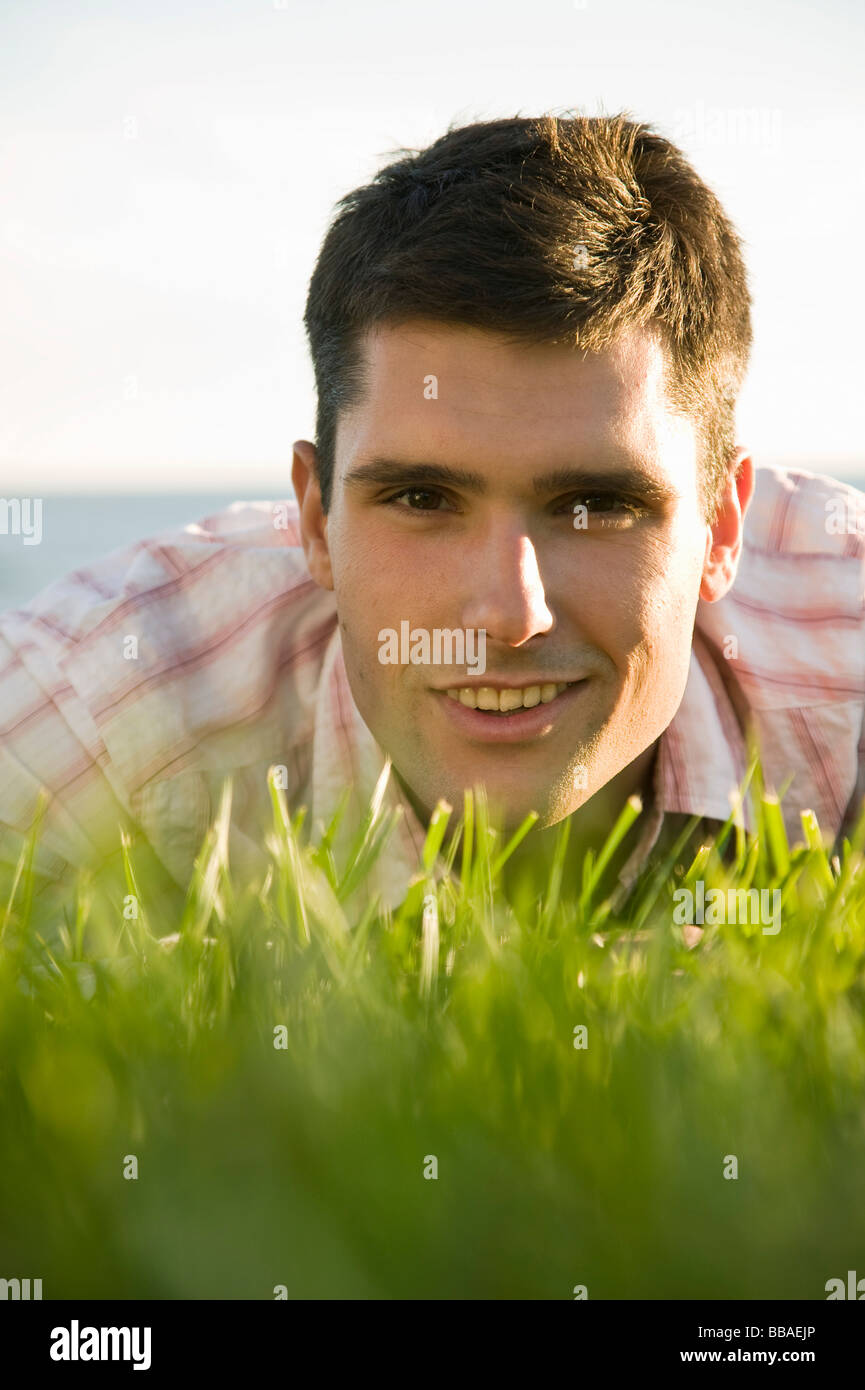 A man lying in grass, heads and shoulders, surface level - Stock Image
