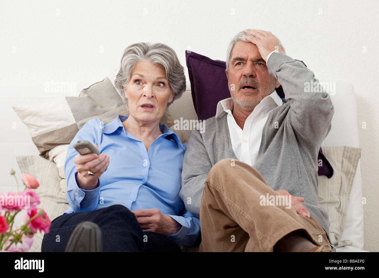 A couple watching something unbelievable on TV - Stock Image