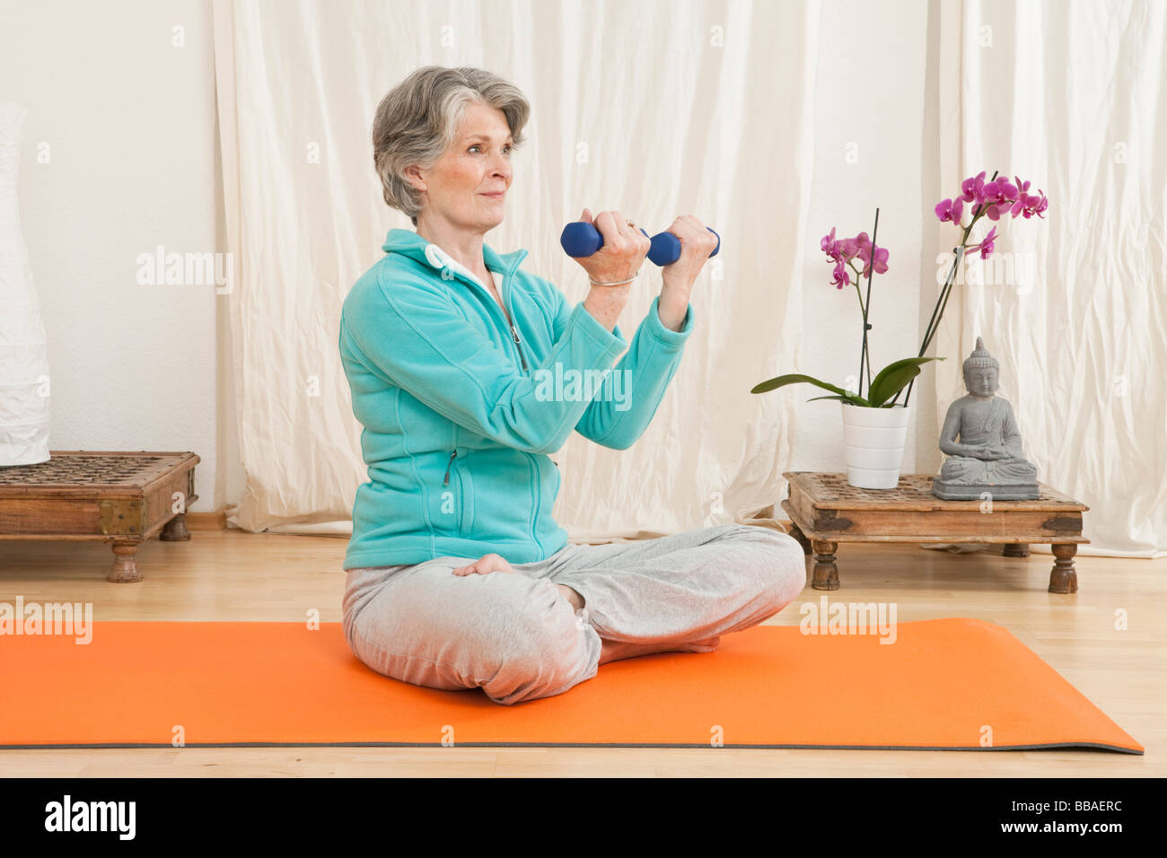 A senior woman working out with hand weights in a yoga studio - Stock Image