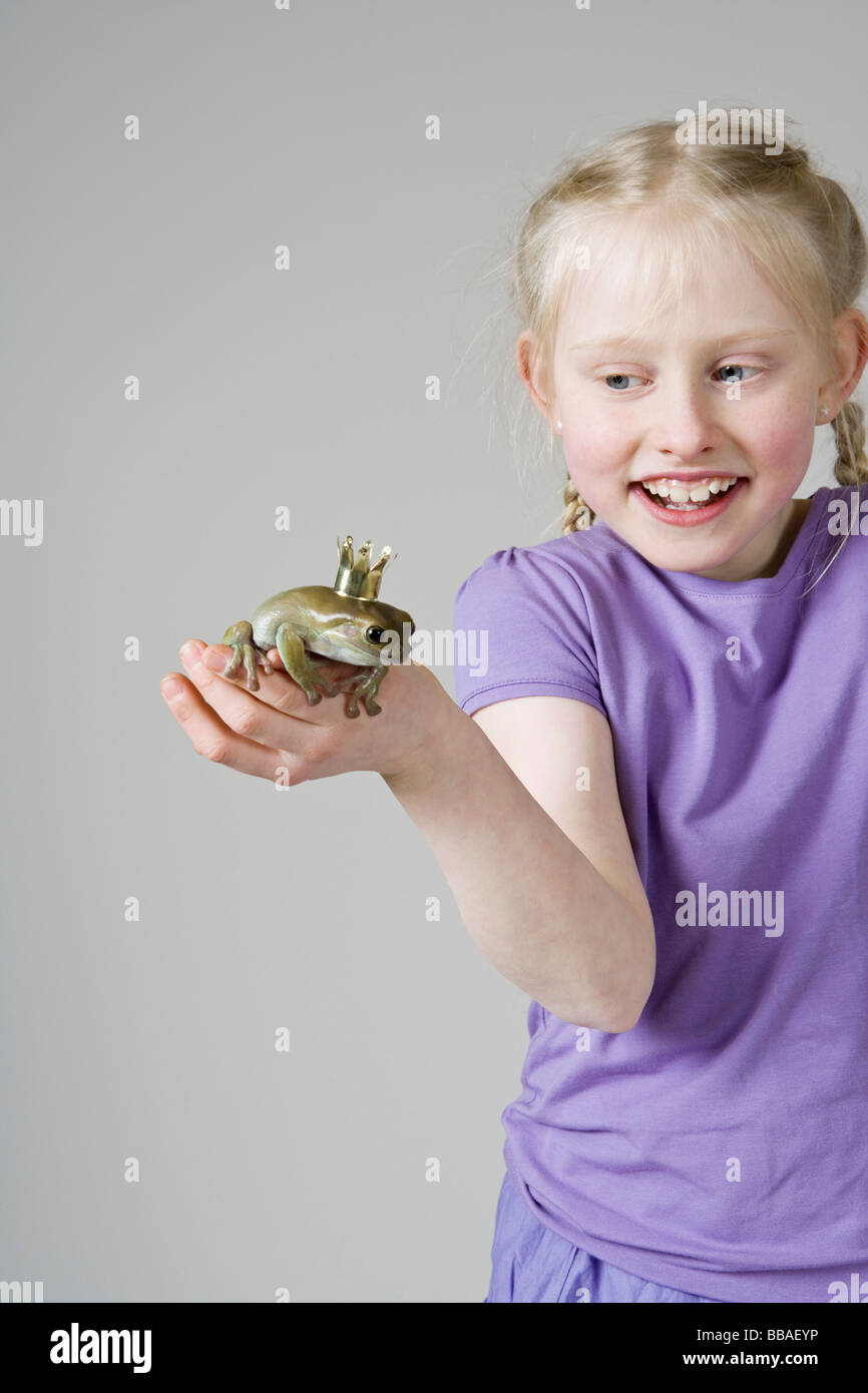 A girl holding a frog prince - Stock Image